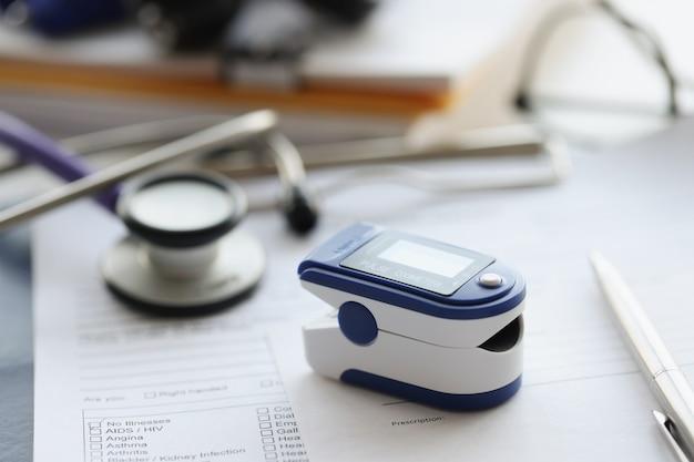 Oxímetro de pulso usado para medir a freqüência cardíaca e os níveis de oxigênio na mesa de controle de freqüência cardíaca diária