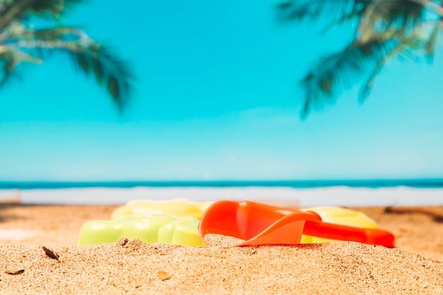 Pá de brinquedo na areia pelo mar