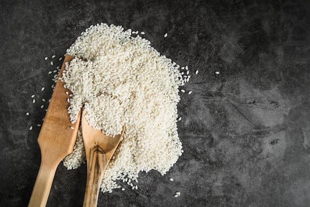 Pá de cozinha de madeira e colher com arroz branco