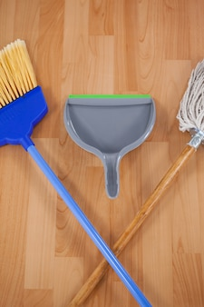 Pá de lixo, vassoura e esfregona no chão de madeira