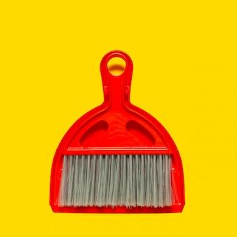Pá de lixo vermelho e escova deitado no fundo amarelo