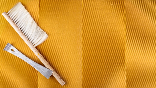 Pá de metal com escova sobre favo de mel