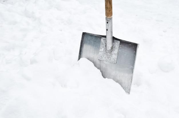 Pá de neve em um monte de neve.