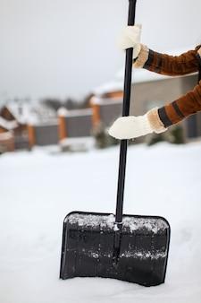 Pá de neve nas mãos femininas em um dia de inverno