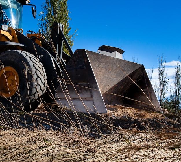 Pá escavadeira limpar estradas de terra e árvores de um desastre natural