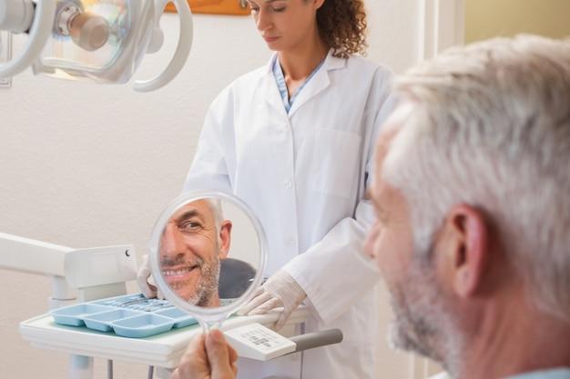 Paciente, admirando o novo sorriso no espelho