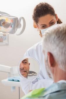 Paciente admirando seu novo sorriso no espelho
