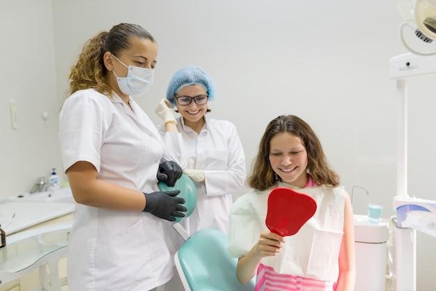Paciente adolescente feliz, olhando no espelho para os dentes