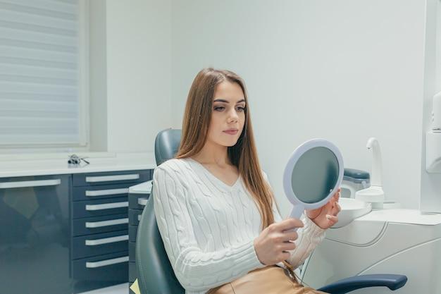 Paciente adulto atraente garota no consultório odontológico olha para os dentes no espelho