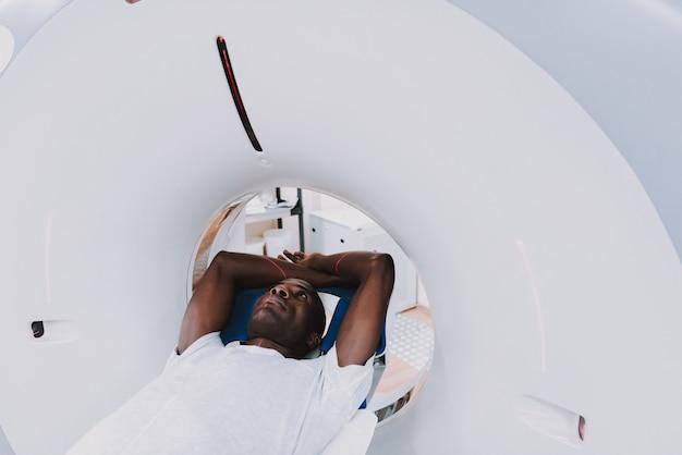 Paciente afro dentro de exame de tomografia