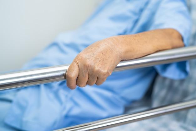 Paciente asiática idosa deitar-se segurando a cama gradeada