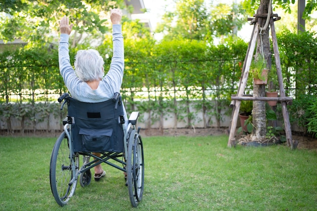 Paciente asiática idosa fazendo exercícios em cadeira de rodas no jardim doméstico
