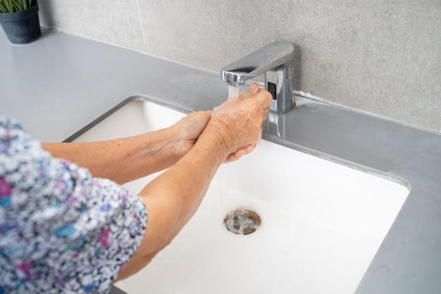Paciente asiática idosa lavando as mãos com sabão e água limpa para proteger covid 19 coronavirus