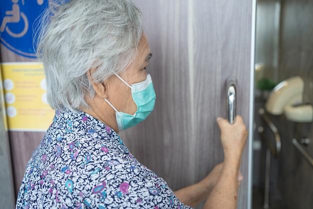Paciente asiática, idosa ou idosa, usando uma máscara facial abre a porta do banheiro para pessoas com deficiência para proteger a infecção de segurança covid-19 coronavirus.