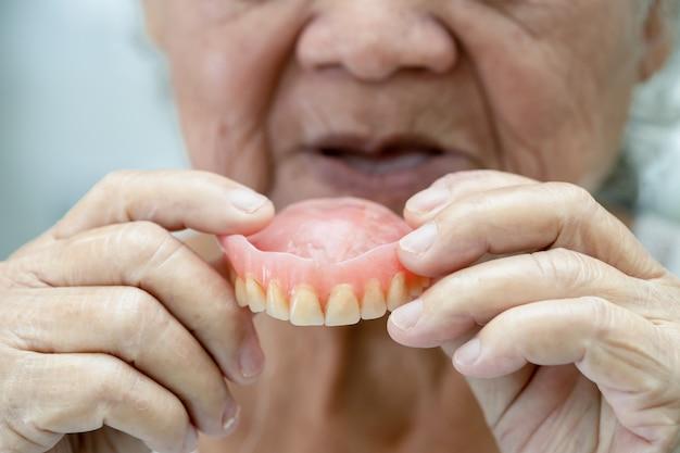 Paciente asiática idosa segurando uma dentadura em hospital de enfermagem