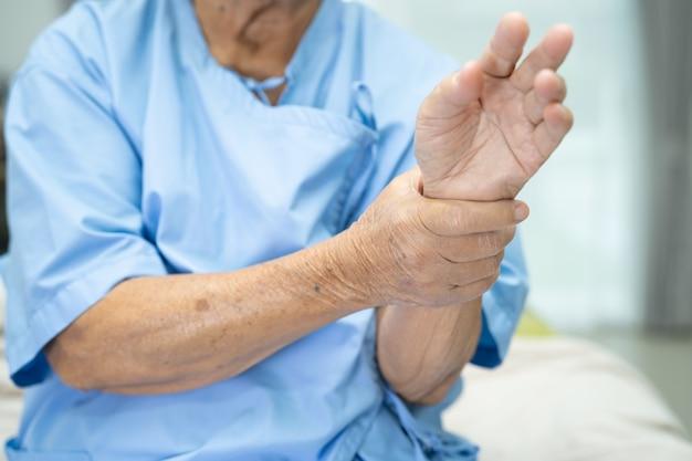 Paciente asiática idosa sente dor no pulso e na mão no hospital