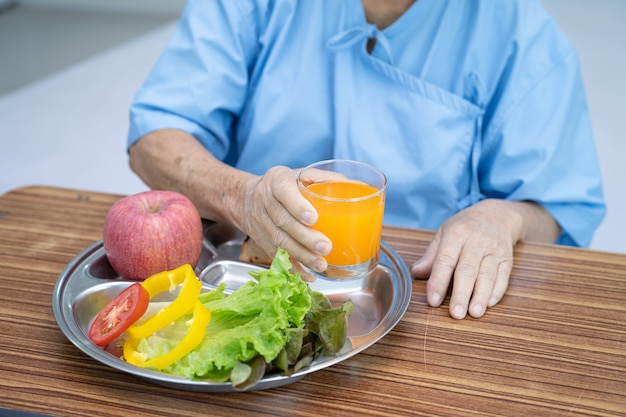 Paciente asiática idosa tomando café da manhã com vegetais saudáveis
