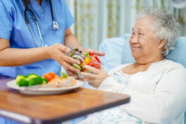 Paciente asiática sênior da mulher comendo alimentos saudáveis café da manhã.