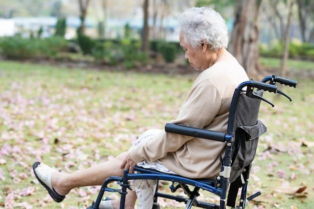 Paciente asiática sênior mulher dor no joelho na cadeira de rodas no parque.
