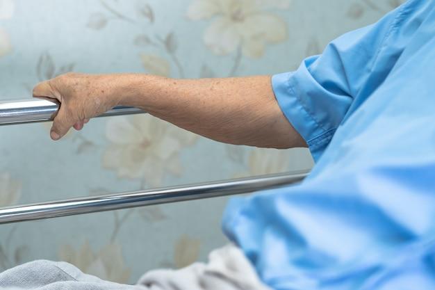 Paciente asiática sênior mulher lida com a cama de trilho em uma cama no hospital