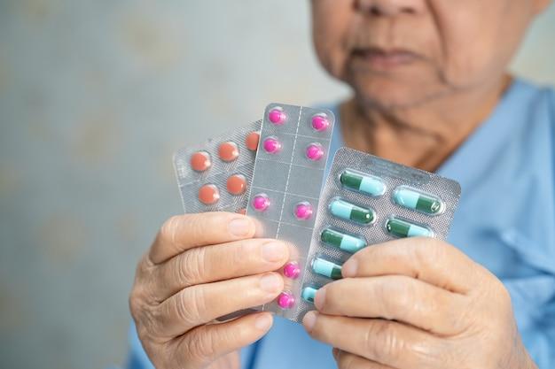 Paciente asiática sênior segurando pílulas de antibióticos em embalagem blister para tratamento
