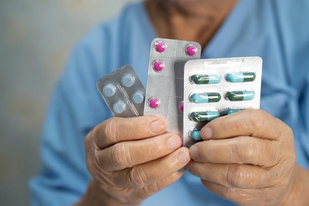 Paciente asiática sênior segurando pílulas de antibióticos em embalagem blister