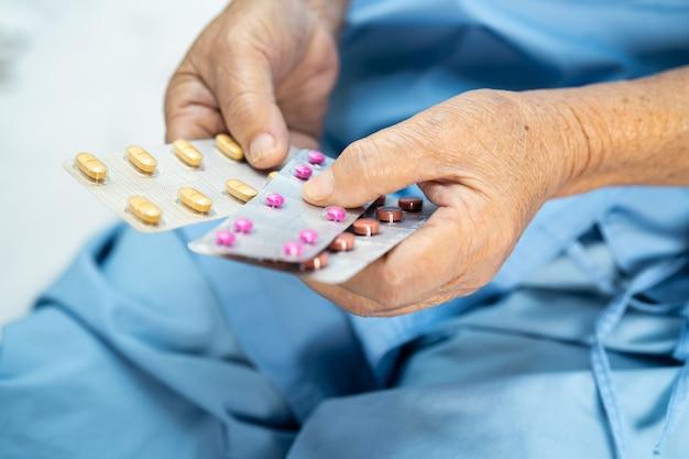 Paciente asiática sênior segurando pílulas de antibióticos no hospital