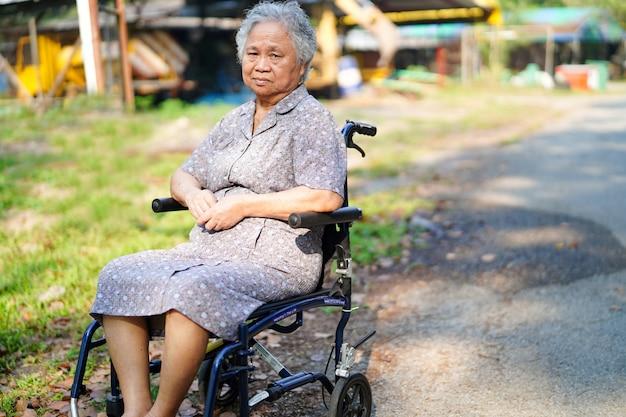 Paciente asiático da senhora na cadeira de rodas no parque.