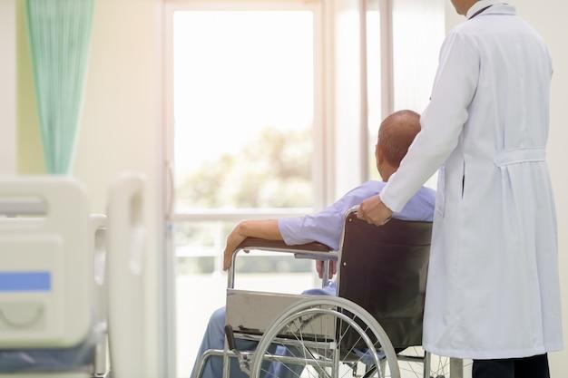 Paciente asiático na cadeira de rodas que senta-se no corredor do hospital com o doutor masculino asiático.