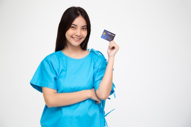 Paciente asiático novo da mulher bonita que mostra o cartão de crédito isolado, apólice de seguro pelo conceito do banco