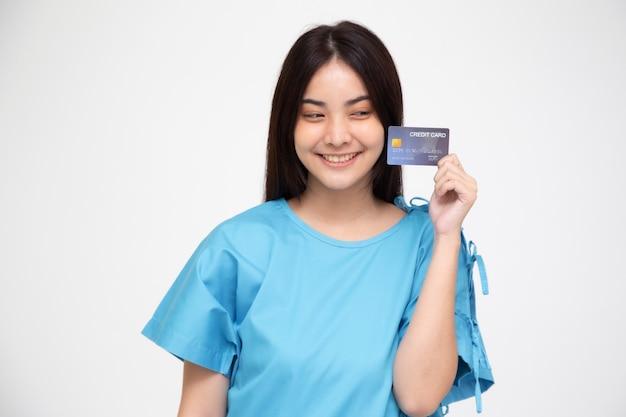 Paciente asiático novo da mulher bonita que mostra o cartão de crédito isolado