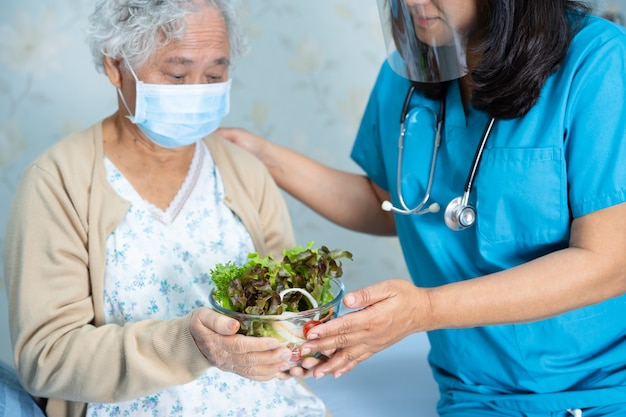 Paciente asiático sênior da mulher segurando vegetais no hospital.