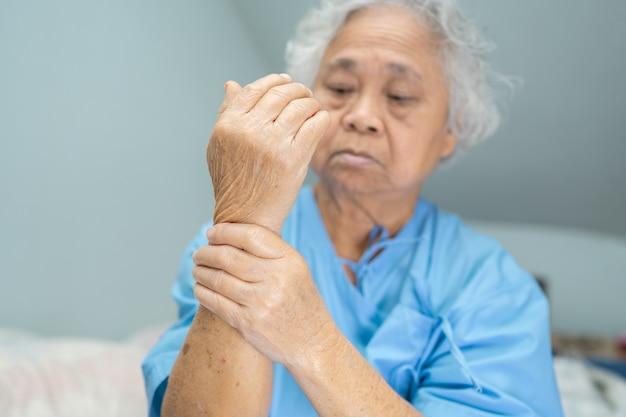 Paciente asiático sênior mulher sente dor na mão no hospital.
