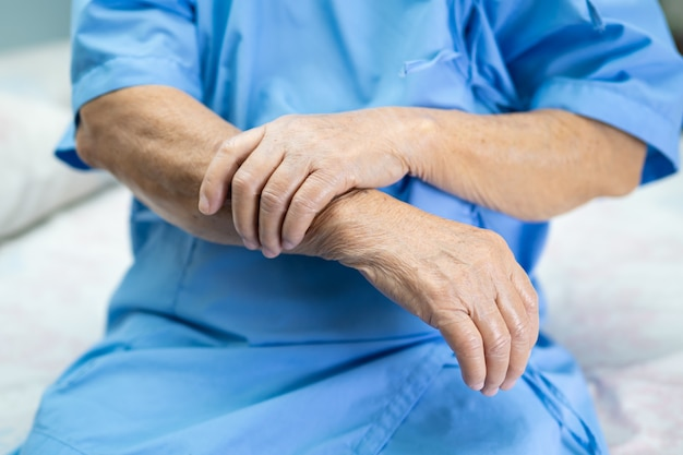 Paciente asiático sênior mulher sente dor no braço no hospital.
