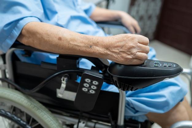 Paciente asiático sênior ou idoso da mulher da senhora idosa na cadeira de rodas elétrica com controlo a distância no hospital.