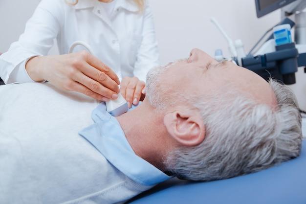 Paciente barbudo sênior imóvel, deitado na maca médica e fazendo exame de ultrassom da tireoide enquanto o médico usa o transdutor linear de ultrassom