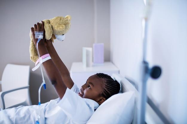 Paciente brincando com ursinho enquanto descansa na cama
