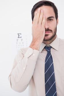 Paciente carrancudo, olhando para a câmera com um olho