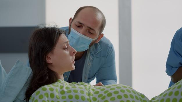 Paciente caucasiana em agonia, dando à luz a criança na enfermaria do hospital