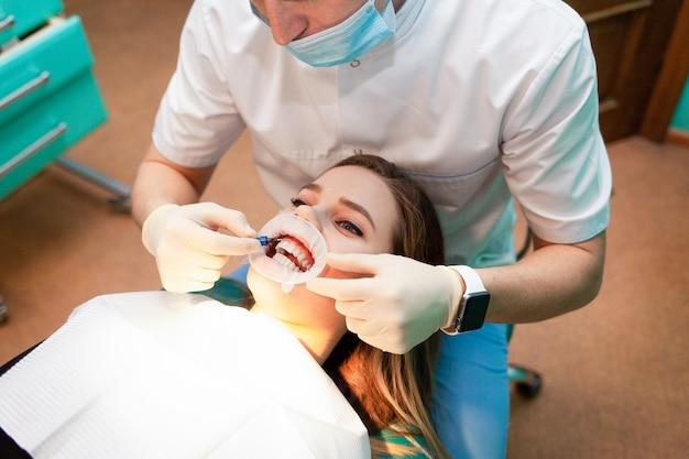 Paciente com afastador da bochecha encontra-se na cadeira odontológica durante o procedimento de clareamento dos dentes