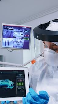 Paciente com explicação de escuta para tratamento dentário, dentista de macacão mostrando raio-x no tablet. especialista em estomatologia usando traje de proteção contra infecção por covid19 apontando para a radiografia