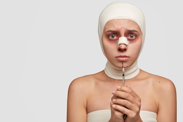 Paciente com medo e medo após uma operação, segura agulha hipodérmica, tem pele machucada, curativo no nariz, espaço em branco à esquerda