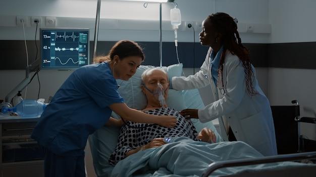 Paciente com problemas respiratórios, desmaio na cama da enfermaria do hospital em uma instalação médica de equipamentos modernos n ...