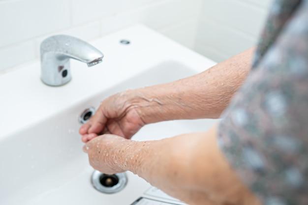 Paciente da mulher sênior asiática lavando as mãos no banheiro.