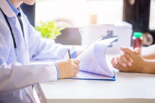 Paciente de consulta do homem do doutor ao encher acima um formulário de candidatura na mesa no hospital.
