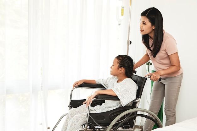 Paciente de criança do sexo feminino em cadeira de rodas