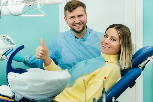 Paciente de linda garota mostra a classe com a mão enquanto está sentado na cadeira do dentista.