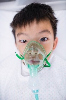 Paciente de menino usando máscara de oxigênio, deitado na cama do hospital