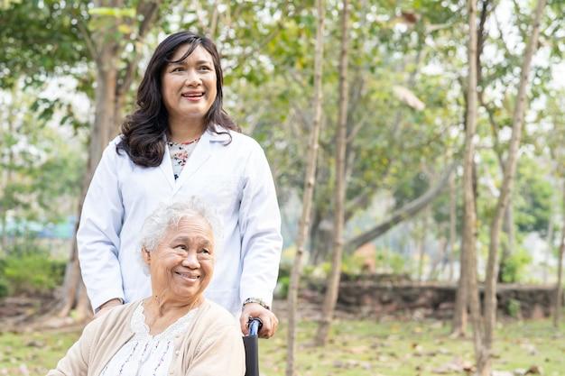 Paciente de mulher idosa asiática sênior ou idosa com cuidado, ajuda e suporte em cadeira de rodas no parque em férias, conceito médico forte e saudável.