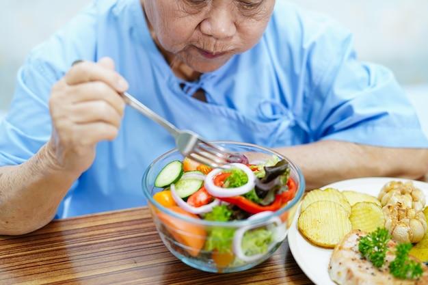 Paciente de mulher idosa asiática sênior ou idosa comendo alimentos saudáveis de vegetais de café da manhã com esperança e feliz enquanto está sentado e com fome na cama no hospital.
